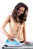 Indian girl and electric steam iron Stock Image