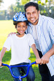 Indian girl father. Young indian girl on a bike with her father standing next to her Royalty Free Stock Photos