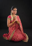 Indian girl in a greeting pose. Traditional sari costume, full length kneeling on floor isolated on black background Royalty Free Stock Photos