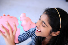 Indian girl holding piggybank Royalty Free Stock Images