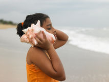Indian girl listening to a conch Stock Photo