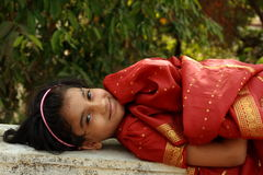 Indian girl lying down. Smiling Indian girl lying down in her traditional dress, a rich red sari, on a park bench stock image