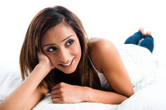 Indian girl lying down, teeth smile and resting Royalty Free Stock Photo