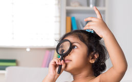 Indian girl peeking through magnifying glass. Cute Indian girl peeking through magnifying glass. Asian child at home Stock Images