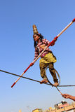 Indian girl performs street acrobatics by walking the rope Stock Images