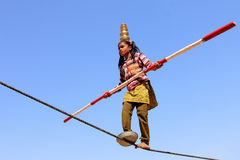 Indian girl performs street acrobatics by walking the rope Stock Photography