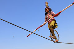 Indian girl performs street acrobatics by walking the rope Royalty Free Stock Image