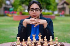 An Indian girl playing chess waiting for the opponent to play and anxiously thinking about her next move. Concept - idea, strategy