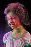Indian girl plays holi. Portrait of Indian girl with colored powder thrown on her face in a dark background. Concept for Indian festival Holi Stock Images