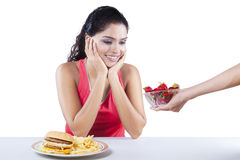 Indian Girl Receive Strawberry. Portrait of indian girl receive strawberry in a bowl with hamburger on the table Royalty Free Stock Photography