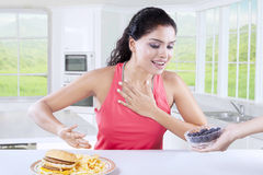 Indian Girl Refuse to Eat Junk Food. Pretty indian woman refuse to eat fast food and choose a bowl of blueberry, shot in the kitchen royalty free stock images