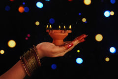 Indian girl's hand holding oil lamp Royalty Free Stock Photos