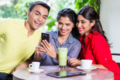 Indian girl showing pictures on phone to friends royalty free stock photos