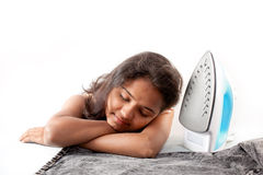 Indian girl sleeping  and electric steam iron Royalty Free Stock Images