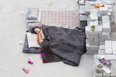 Indian girl sleeping on the street next to monastery of Lamayuru, Ladakh, India Royalty Free Stock Images