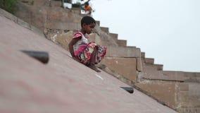 Indian girl sliding down the slope on ghats of Ganges river in Varanasi. VARANASI, INDIA - 19 FEBRUARY 2015: Indian girl sliding down the slope on ghats of stock video