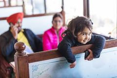 Indian girl smiles with her parents in the background at dinning room of hotel in Darjeeling in winter, India Stock Photography