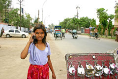 Indian girl talking on her mobile phone at a roadside shop Royalty Free Stock Photography