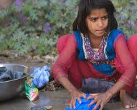 Indian Girl Washing Clothes. NIMAJ BAGH, INDIA, FEBRUARY 28: An unidentified girl washing clothes by hand inside the village of Nimaj Bagh, Rajasthan, Northern Stock Photo