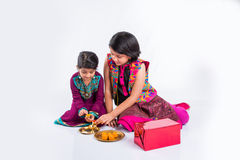 Indian girls decorating pooja thali. Two cute indian small girls in traditional wear preparing pooja thali or puja thali Royalty Free Stock Image