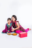Indian girls decorating pooja thali. Two cute indian small girls in traditional wear preparing pooja thali or puja thali Royalty Free Stock Photo