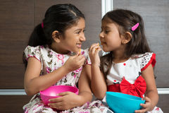 Indian girls eating. Two cute Indian girls eating murukku. Asian sibling or children living lifestyle at home Royalty Free Stock Photography