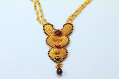 Indian Gold necklace. Front view of a peice of indian jewelery with intricate gold handicraft stock photo