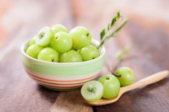 Indian gooseberry fruit in a bowl. And spoon on wooden background.Healthy and highest vitamin C fruit stock photos