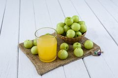 Indian gooseberry on wooden table. Indian gooseberry in Wicker basket and juice, Sackcloth on white wooden table royalty free stock image