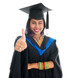 Indian graduate student giving thumb up hand sign. Happy Indian graduate student in graduation gown and cap giving thumb up hand sign. Portrait of beautiful Royalty Free Stock Images