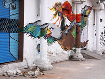 Indian Graffitti. NEW DELHI, INDIA – MARCH 14, 2015: Stray dogs asleep under graffiti in the central Connaught Place district. Packs of street dogs are found Stock Photography