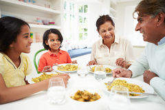 Indian Grandparents And Grandchildren Eating Meal At Home. Sitting Down Smiling stock photo