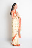 Indian greeting pose. Full length mixed race Indian Chinese woman with sari dress in greeting gesture, standing on plain background Royalty Free Stock Photos
