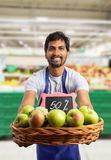 Grocery store employee offering apples from basket. Indian grocery store or supermarket male employee smiling as offering apples at half price from basket stock images