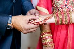 Indian groom putting ring on indian bride. In Engagement Program Stock Image
