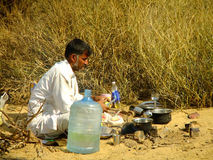 Indian guide cooking for tourists during camel safari in Thar de Stock Image
