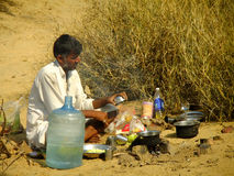 Indian guide cooking for tourists during camel safari Stock Photography