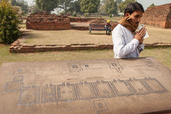 The Indian guide keep his earned money. Archaeological heritage of India, ruins of university of Nalanda on February 2, 2014. At a stone with the scheme of Stock Image