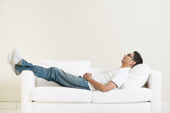 Indian guy daydreaming. And rest at home. Asian man relaxed and sleep on sofa indoor. Handsome male model Stock Images
