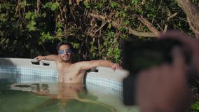 Indian Guy in Diving Goggles Posing in the Children`s Pool for Photography. Indian Guy with Naked Torso and Diving Goggles Posing in the Children`s Pool for stock video footage