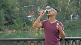 Indian Guy in Glasses Puffs Big Soap Bubble and Rejoices. On River Embankment stock video footage