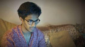 Indian Guy In Glasses Sits On Sofa And Looks At Laptop Monitor Screen. Indian Guy In Glasses Sits On The Sofa And Looks At The Laptop Monitor Screen stock video
