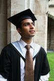 Indian guy in a graduation gown. Royalty Free Stock Images