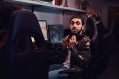 A young Indian guy wearing a military shirt sitting on a gamer chair and looking at a camera in a gaming club or. A Indian guy wearing a military shirt sitting royalty free stock photos