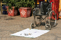 Indian Handicapped man places a wheelchair in a public place to sit on and seek alms Stock Photo