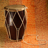 Indian handmade drum. Brown indian drum on an orange background Royalty Free Stock Photo