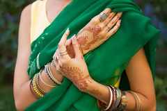Indian hands with mehendi draws and bracelets royalty free stock image