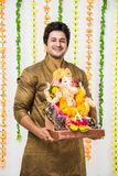 Indian handsome man in ethnic wear holding a Ganesh idol, welcoming God on Ganesh Chaturthi / festival at home with happy expressi Royalty Free Stock Images