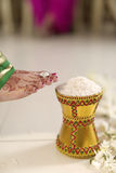 Indian Hindu Bride entering groom's home after wedding by pushing pot filled with rice with her foot. Royalty Free Stock Photos