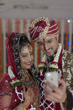 Indian Hindu Bride & Groom a happy smiling couple shooting self with mobile. Royalty Free Stock Photography